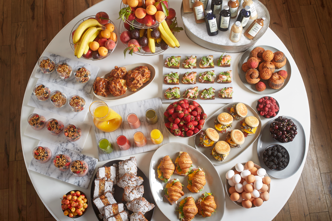Breakfast Buffet with an assortment of Croissant Sandwiches, Yogurt Parfaits, Pastries, Hot Breakfast Sandwiches, Avocado Toast, Iced Coffees, Fresh Fruit and Juices